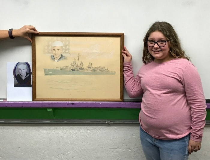 Emily with a picture of her grandfather and his naval ship.